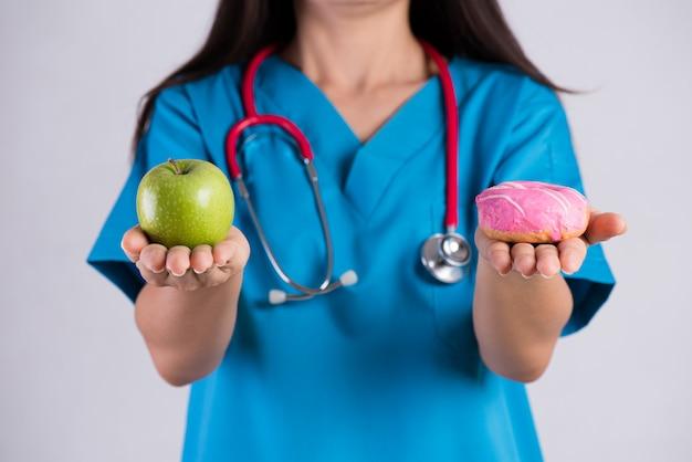 Doktorfrauenhand, die donut und grünen apfel hält Premium Fotos