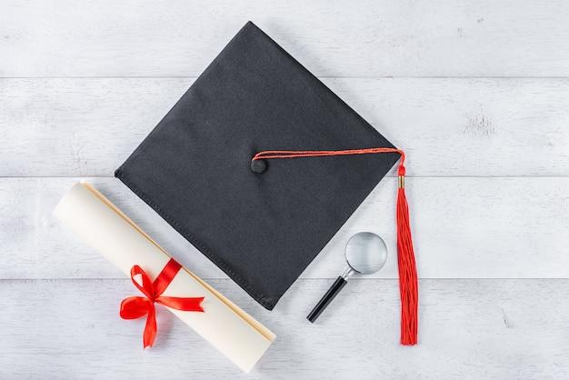Doktorhut, lupe und diplom gebunden mit rotem band auf weißem holztisch, draufsicht Premium Fotos