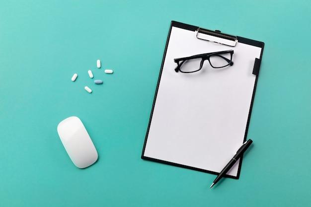 Doktorschreibtisch mit tablette, stift, maus und pillen Premium Fotos