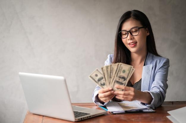 Dollar in der hand einer geschäftsfrau. eine asiatische frau arbeitet von zu hause oder vom büro aus und freut sich, geld von der arbeit und von einer zusätzlichen karriere oder einer teilzeit-selbstständigkeit zu bekommen. Premium Fotos