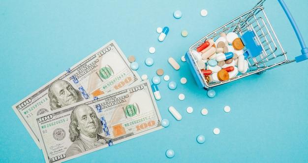 Dollar, pillen und einkaufswagen auf blauem grund. apothekenkonzept. speicherplatz kopieren. Premium Fotos