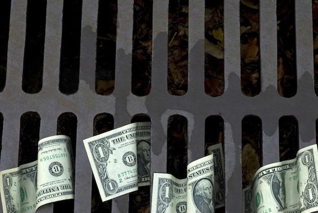Dollar-scheine in einer straße drain Kostenlose Fotos
