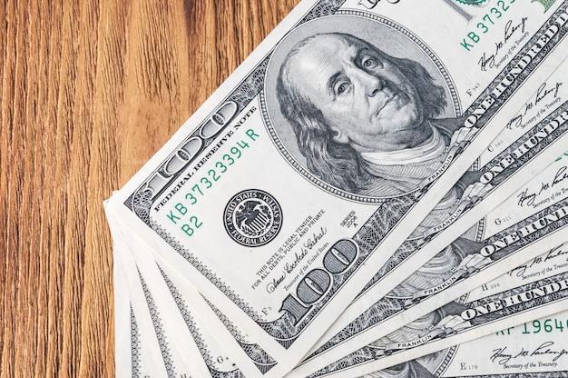 Dollarbanknoten im fan am hölzernen hintergrund. Premium Fotos