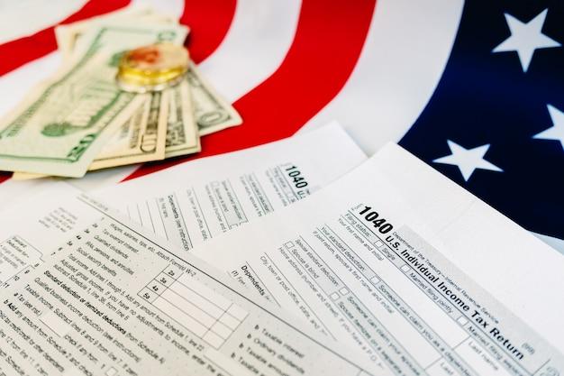 Dollarnoten auf einem tisch, auf dem das zahlungsformular für 1040 amerikanische steuern ausgefüllt ist. Premium Fotos