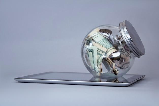 Dollarnoten in einem sparschwein aus glas auf einer tablette. Premium Fotos