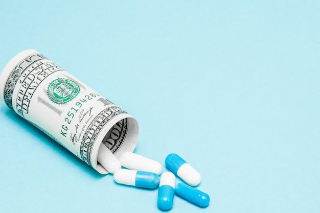 Dollarschein rollte oben mit den pillen, die heraus fließen Premium Fotos
