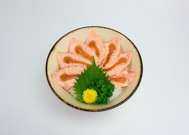 Donburi schnitt den rohen lachs, der mit der saikyo soße geraucht wurde, die mit japanischem reis eingestellt wurde Premium Fotos