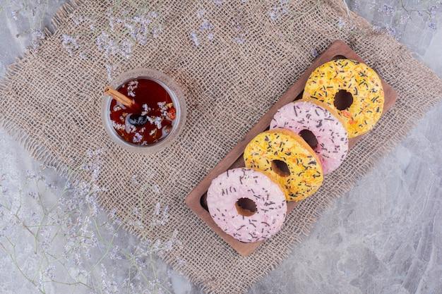 Donut brötchen auf einer holzplatte mit einer tasse glitzern Kostenlose Fotos