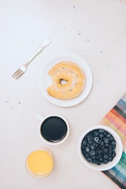 Donut mit biss fehlt; saft; kaffeetasse und blaue beeren auf weißem hintergrund Kostenlose Fotos