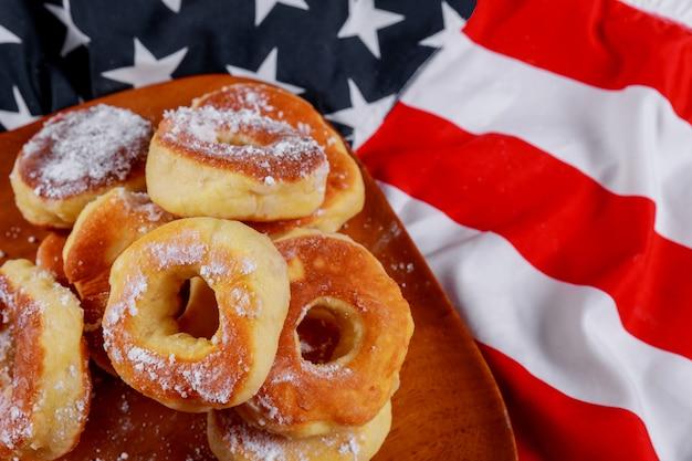 Donut und amerikanische flagge am amerikanischen unabhängigkeitstag der hölzernen platte, feier Premium Fotos
