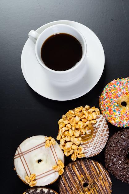 Donut und kaffee auf dem schwarzen hintergrund Premium Fotos