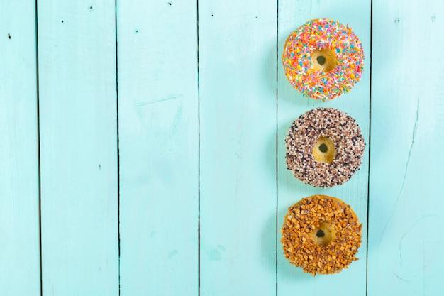 Donuts auf hölzernen hintergrund Premium Fotos