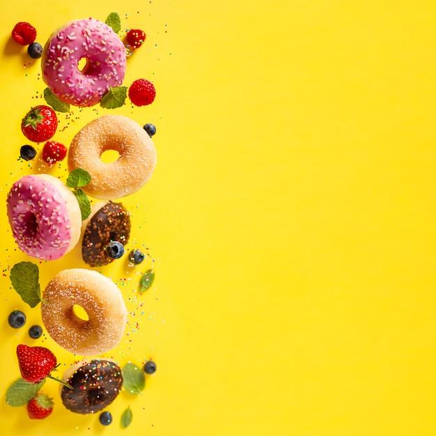 Donuts mit streuseln und beeren in bewegung auf gelbem grund fallen Premium Fotos