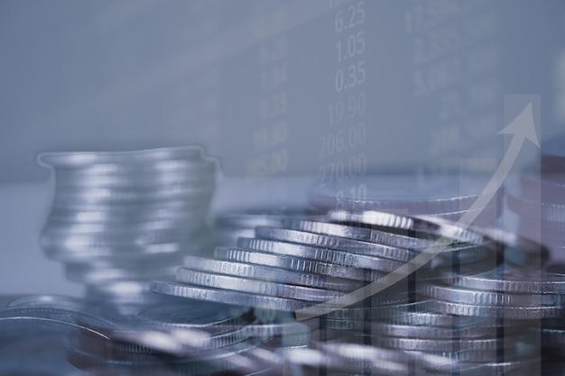 Doppelbelichtung des münzenstapels mit börseenschirm-diagrammbrett Premium Fotos