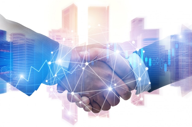 Doppelbelichtungsbild des investorgeschäftsmannhändedrucks mit partner mit digitaler network link-verbindung und diagrammdiagramm des börse- und stadtbildhintergrundes Premium Fotos