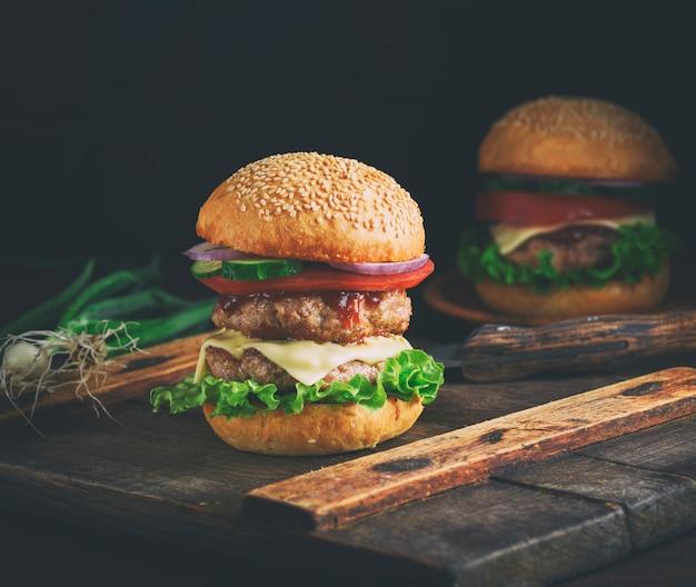 Doppelter cheeseburger in einem brötchen mit samen des indischen sesams Premium Fotos