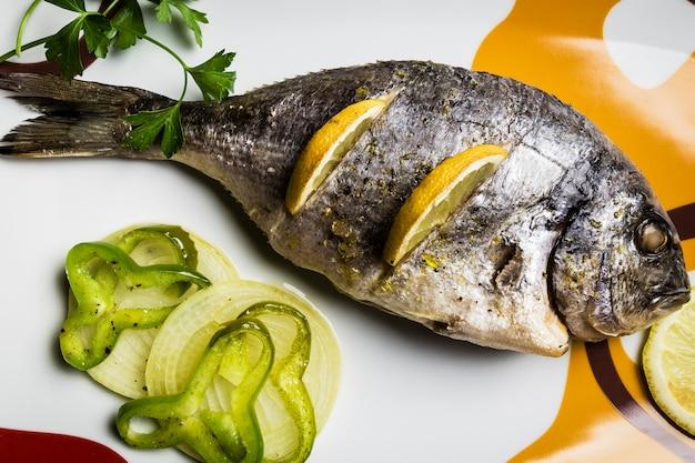 Dorada-fische, die im ofen mit zitrone, piment und frühlingszwiebel gekocht wurden, dienten auf einem behälter auf einem holztisch Premium Fotos