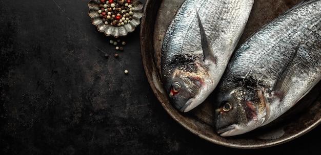 Dorado fisch mit zutaten auf dunkel Kostenlose Fotos