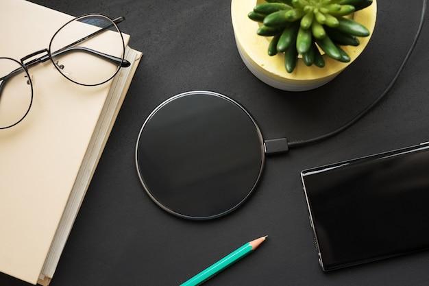 Drahtloses laden auf einer schwarzen tafel mit einem buch, einem bleistift, einem smartphone, einer brille und einer pflanze. Premium Fotos
