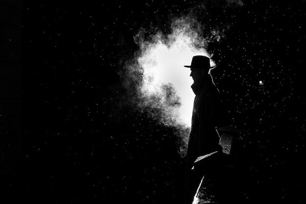 Dramatische silhouette eines gefährlichen mannes in einem hut in der nacht im regen in der stadt im alten verbrechen noir-stil Premium Fotos