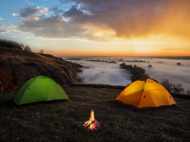 Dramatischer sonnenuntergang über dem fluss und zelten mit einem feuer Premium Fotos
