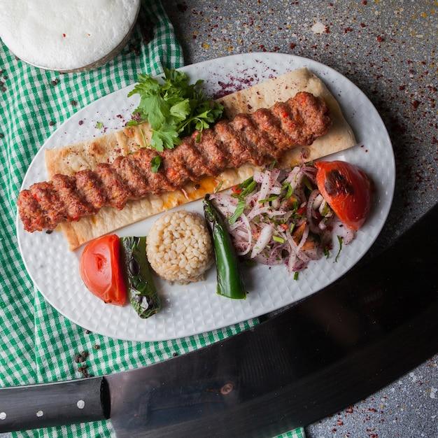 Draufsicht adana kebab mit reis und gebratenem gemüse und gehackten zwiebeln und ayran in weißer platte Kostenlose Fotos