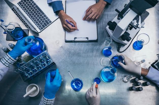 Draufsicht arbeitsbereich im labor mit mikroskop, laptop und laborwerkzeugen Premium Fotos