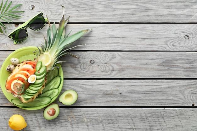 Draufsicht auf ananasboote mit geräucherten lachs- und avocadoscheiben mit zitronen- und wachteleiern, flach auf altem holztisch liegend Premium Fotos