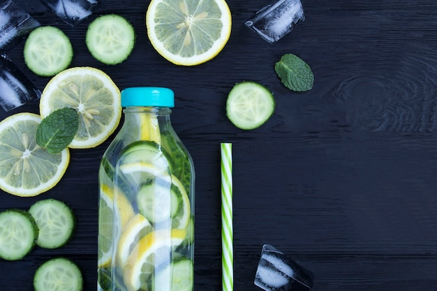 Draufsicht auf aufgegossenes wasser mit zitronengurke und minze in der flasche Premium Fotos