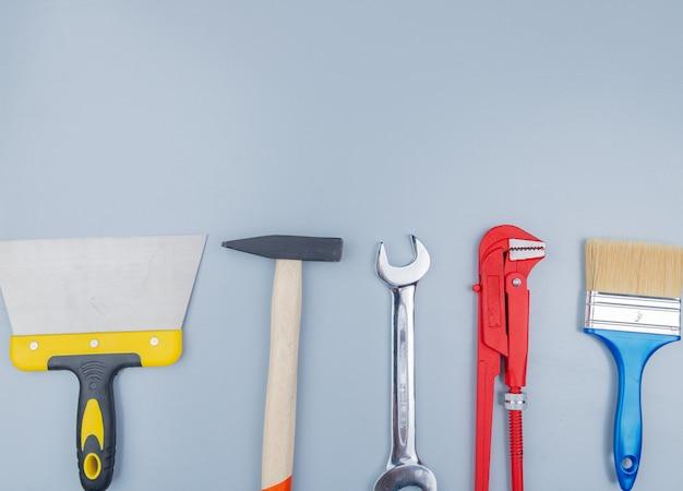 Draufsicht auf bauwerkzeuge als backsteinhammerrohrschlüssel-spachtelmesserpinsel und gabelschlüssel auf grauem hintergrund mit kopierraum Kostenlose Fotos