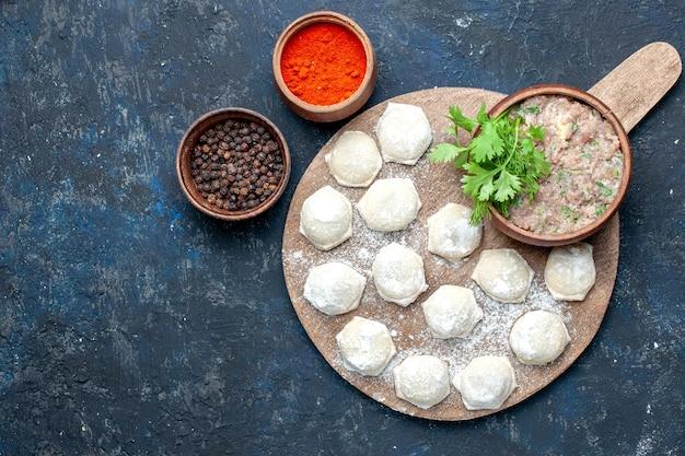 Draufsicht auf bemehlte teigstücke mit hackfleischgrün und paprika auf dunklem teigfleisch-rohfleisch-abendessengebäck Kostenlose Fotos