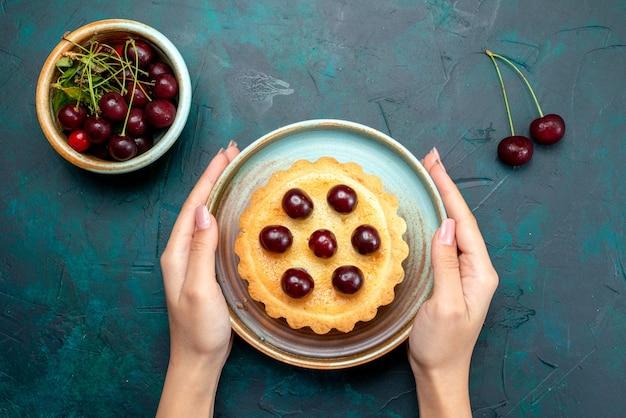 Draufsicht auf cupcake mit verzierten kirschen, die jemand auf tisch legte Kostenlose Fotos