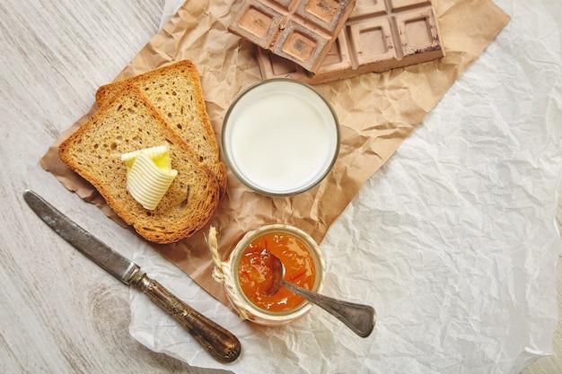 Draufsicht auf das frühstücksset mit schokolade, marmelade, trockenem toastbrot, butter und milch. alles auf bastelpapier und vintage messer und löffel mit patina. Kostenlose Fotos