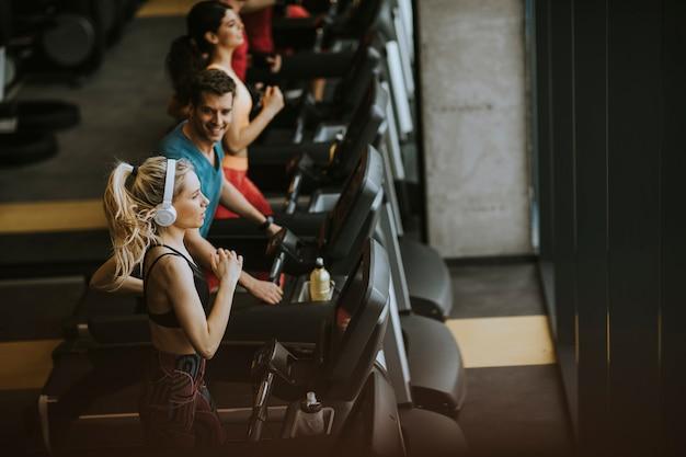 Draufsicht auf die jungen leute, die auf tretmühlen in der modernen turnhalle laufen Premium Fotos