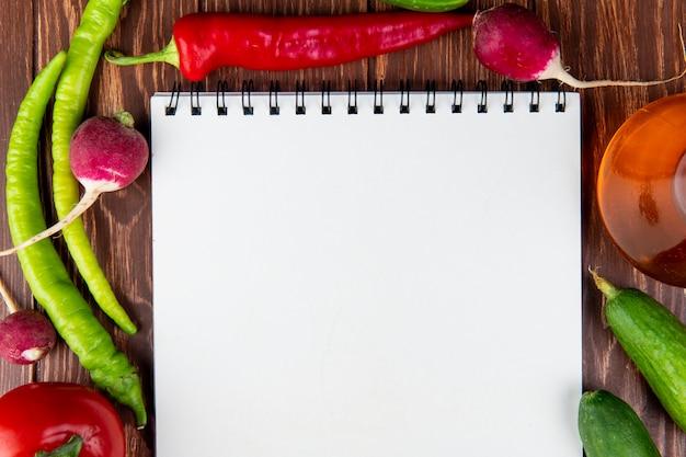 Draufsicht auf ein skizzenbuch und gemüse-chilischoten-radieschen und gurken auf rustikalem holz Kostenlose Fotos