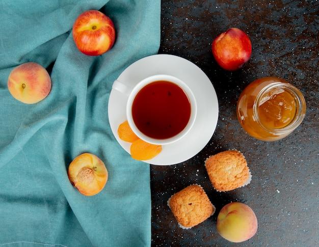 Draufsicht auf eine tasse tee mit getrockneten aprikosen und frischen reifen pfirsichen auf blauem stoff und muffins mit einem glas pfirsichmarmelade auf schwarz Kostenlose Fotos