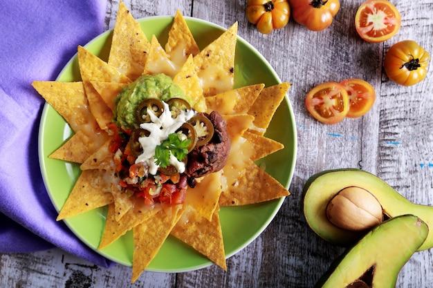 Draufsicht auf einen teller mit hausgemachten corn chips mit vegetarischem bohnen-chili, mozarella und jalapenos am holztisch Premium Fotos