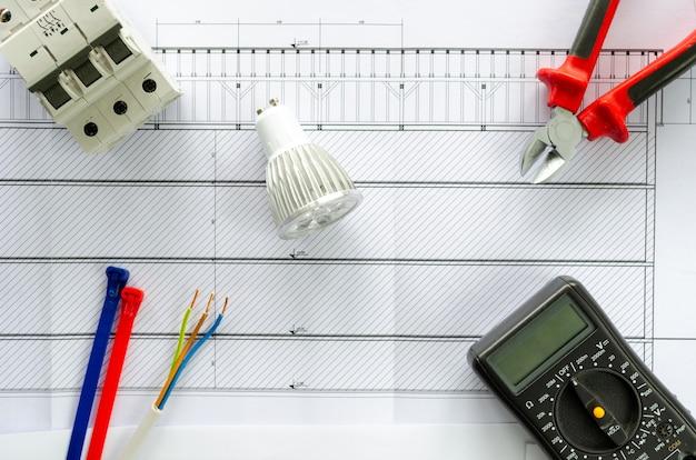 Draufsicht auf elektrische werkzeuge und materialien für elektrische anlage, zange, kabel, led-lampe, voltmeter und schutzbrille auf weißem hintergrund Premium Fotos