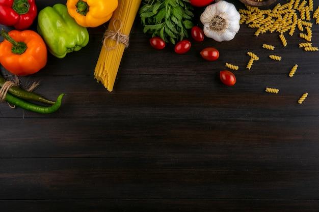 Draufsicht auf farbige paprika mit rohen spaghetti und nudelknoblauch und tomaten auf einer holzoberfläche Kostenlose Fotos