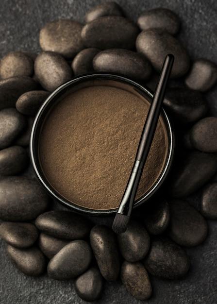 Draufsicht auf feines pulver in schüssel mit pinsel und steinen Premium Fotos