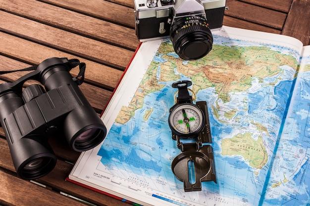 Draufsicht auf fernglas, kompass, fotoapparat und karte Premium Fotos