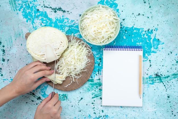 Draufsicht auf frisch geschnittenen kohl mit halb ganzem gemüse, das geschnitten wird und notizblock auf hellblauem schreibtisch, gemüsesalatmahlzeit-gesunder salat Kostenlose Fotos