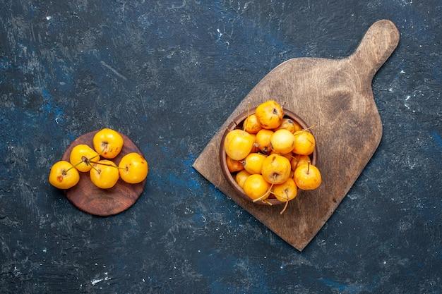 Draufsicht auf frische gelbe kirschen reife süße früchte auf dunklem boden frucht milde frische süßkirsche Kostenlose Fotos
