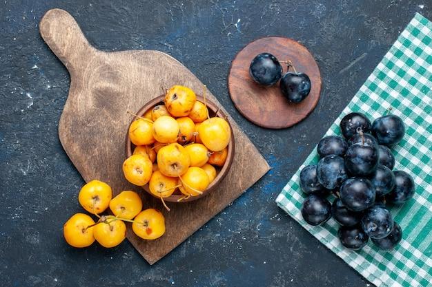Draufsicht auf frische gelbe kirschen reife süße früchte mit schwarzdorn auf grau-dunklem schreibtisch, frucht milde frische süße kirsche Kostenlose Fotos