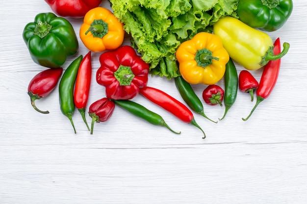 Draufsicht auf frischen grünen salat zusammen mit paprika und würzigen paprikaschoten auf leichtem schreibtisch, zutat für gemüsemahlzeiten Kostenlose Fotos