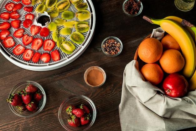 Draufsicht auf frisches fruchtsortiment auf hölzernem küchentisch einschließlich geschnittener kiwi und erdbeeren auf tablett mit trockner und aromatischen gewürzen Premium Fotos