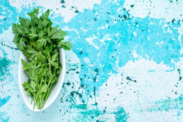 Draufsicht auf frisches grün, das innerhalb der platte auf hellblauem bodengrünblattproduktlebensmittelmehl isoliert wird Kostenlose Fotos
