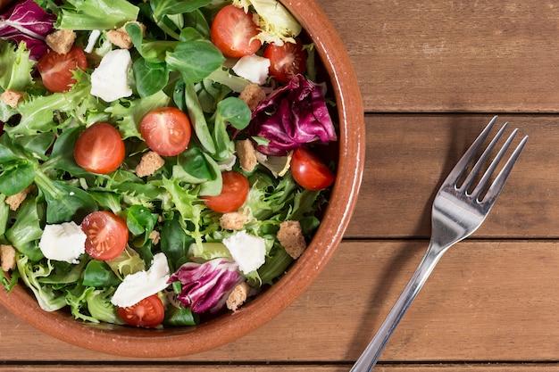 Draufsicht auf gabel neben einer schüssel mit salat Kostenlose Fotos