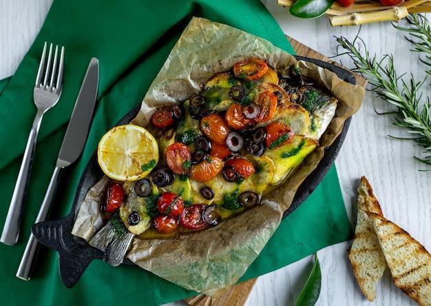 Draufsicht auf gebratenen fisch mit kartoffeln, kirschtomaten, oliven und zitrone gekrönt Kostenlose Fotos