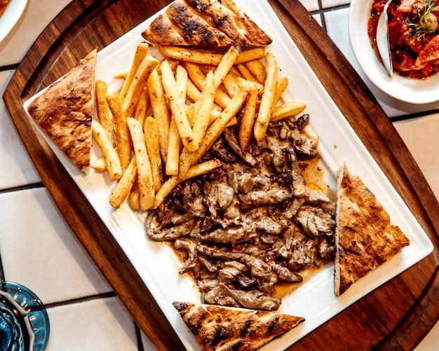 Draufsicht auf gegrillte rindfleischstücke, serviert mit pommes frites und geröstetem tandoorbrot Kostenlose Fotos
